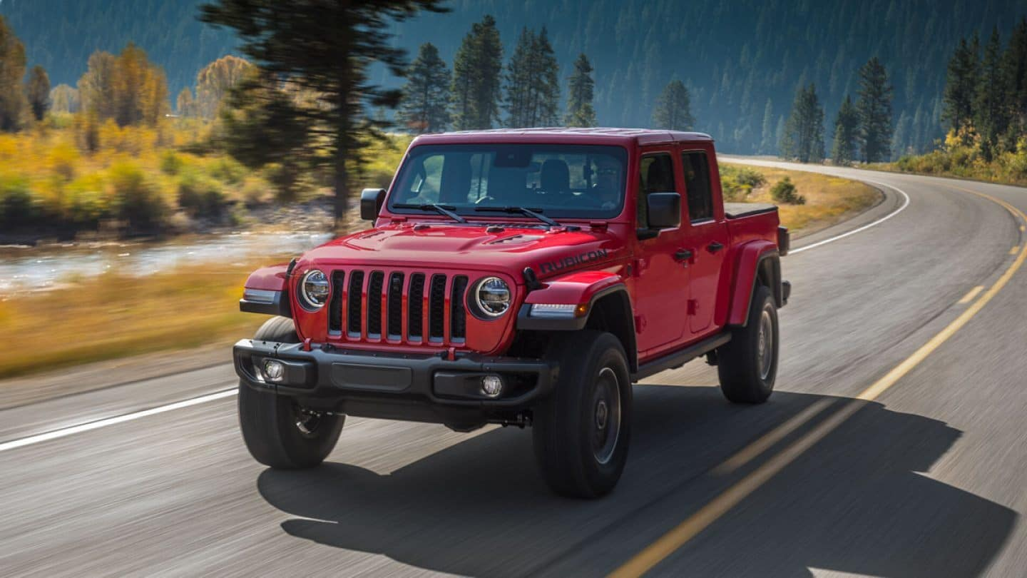 A Red Jeep Gladiator dring down an open forest road