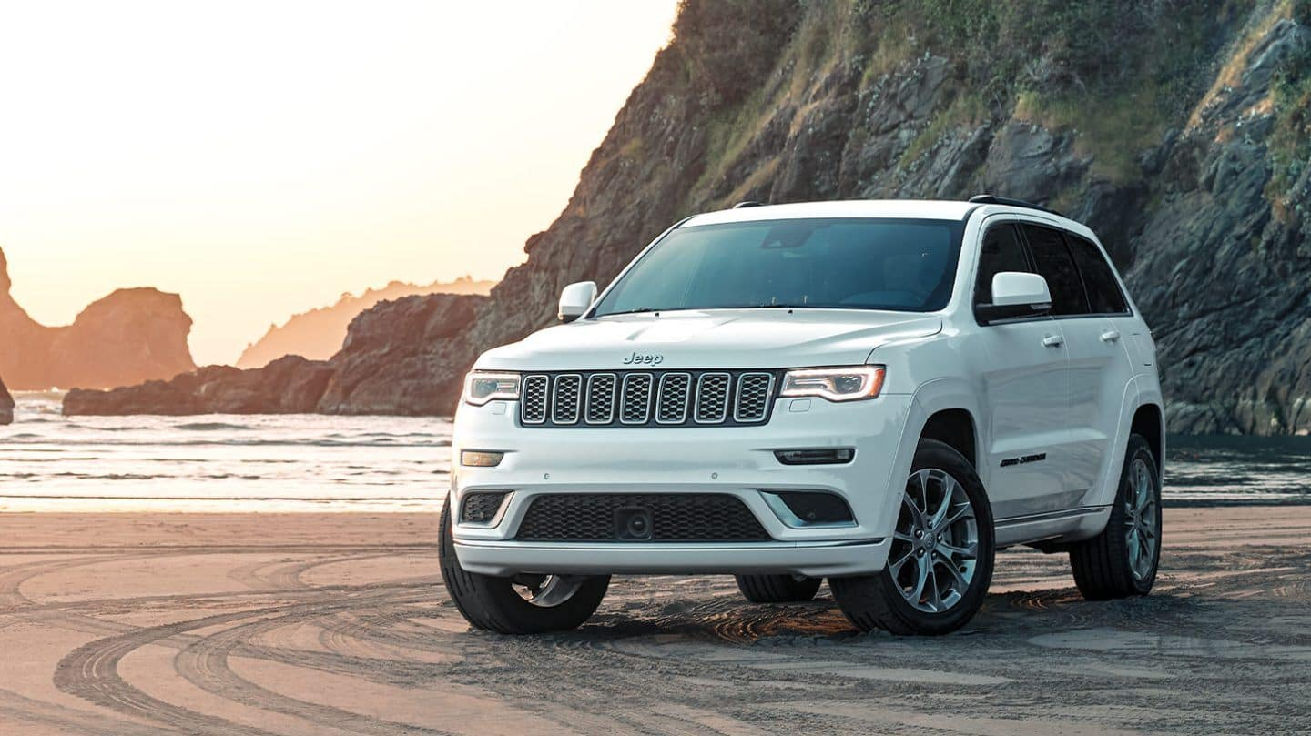 A white 2020 Jeep Grand Cherokee parked on a beach