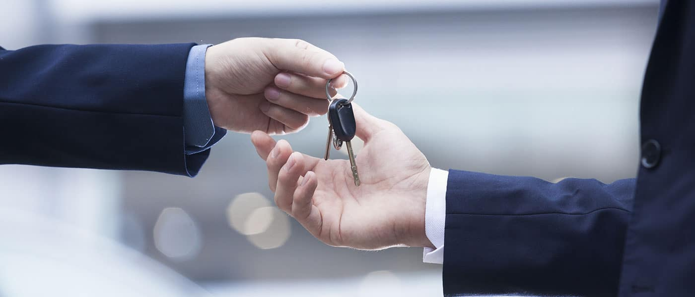 One person handing car keys to another