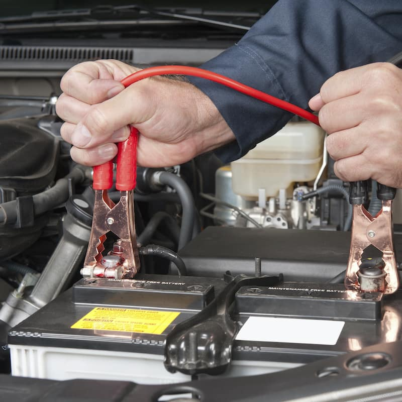 A mechanic connecting a car battery