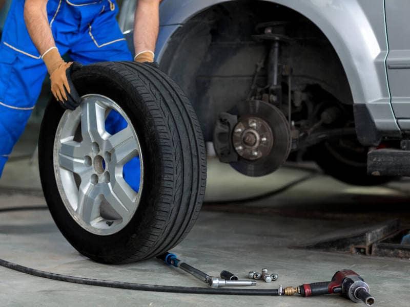 A mechanic moving a tire