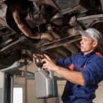 Car mechanic draining motor oil under lifted car at repair service station