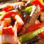 Steak fajitas sizzling in a cast iron pan