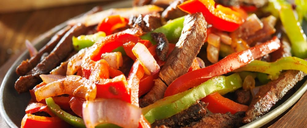 Steak fajitas sizzling in a cast iron pan