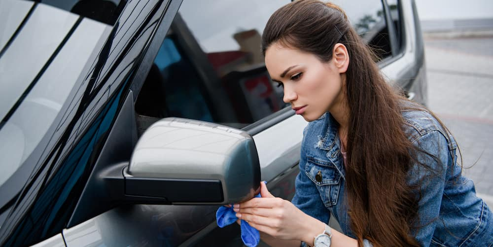 Woman Wiping Down Car Mirror