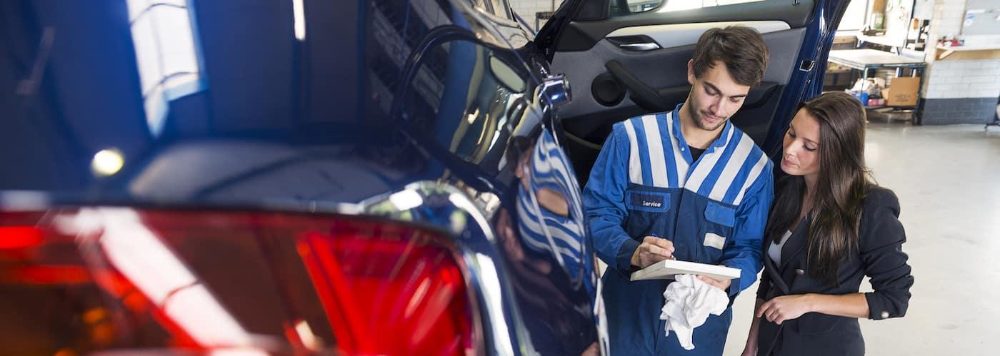 Car Mechanic Going Over Checklist