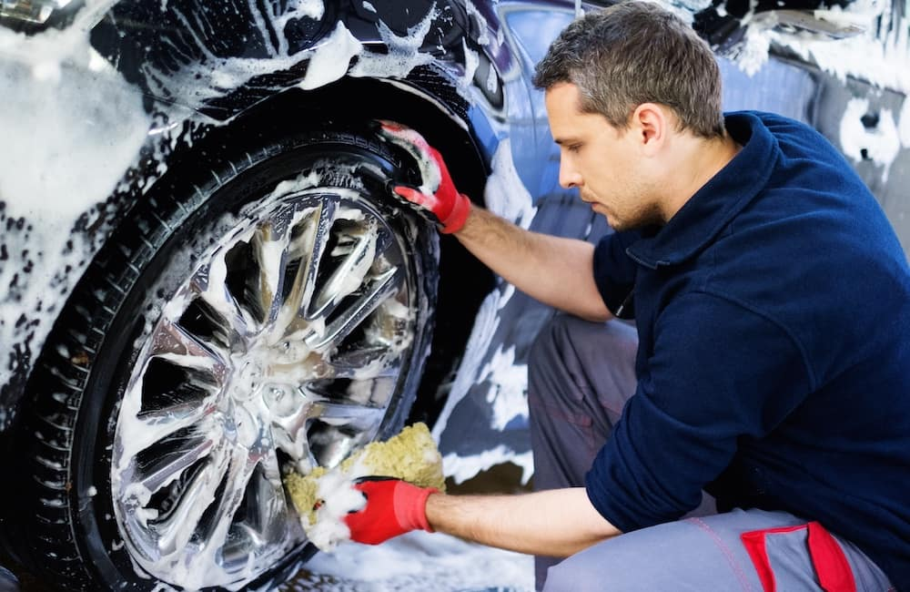 Man Cleaning Car Wheels by Hand