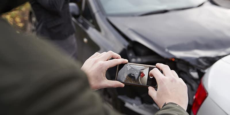 Man taking photos of car accident damage
