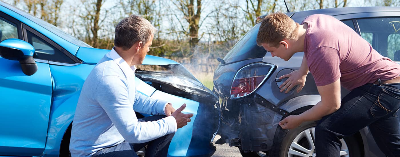 Men looking at damage from car accident