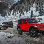 Red and Gray Jeep Wranglers in Snowy Mountains