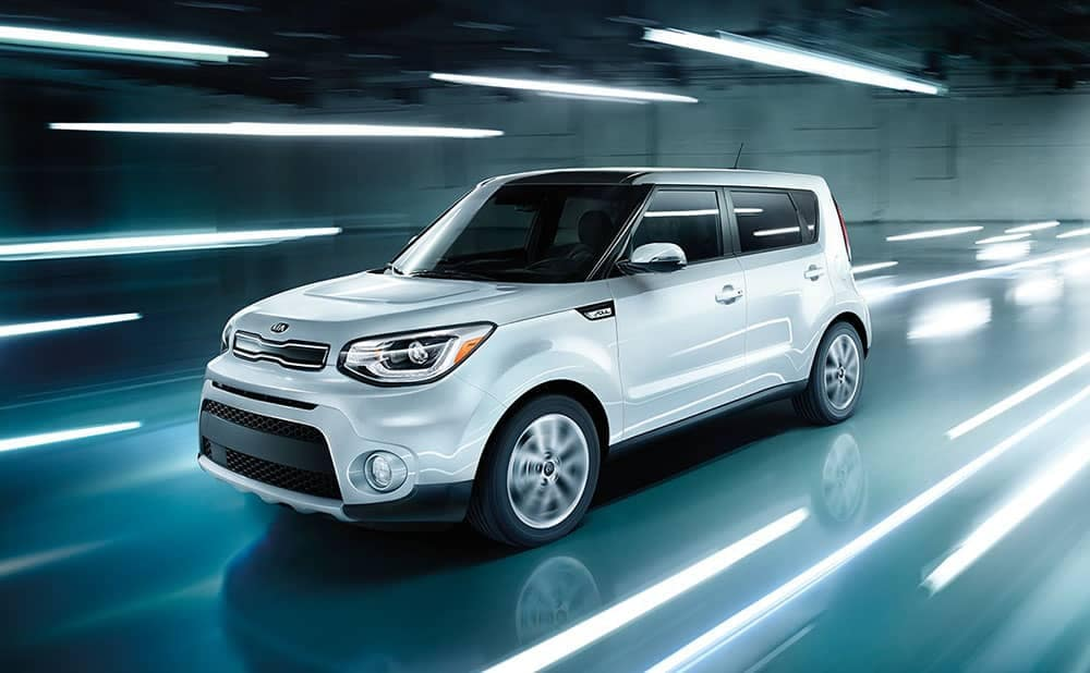 White Kia Soul driving through lit tunnel