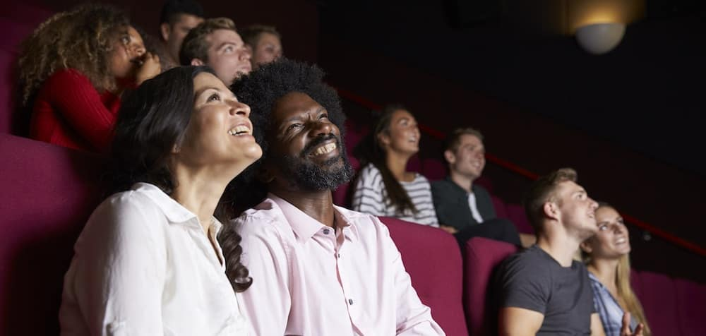 People laughing and watching a movie in a theater