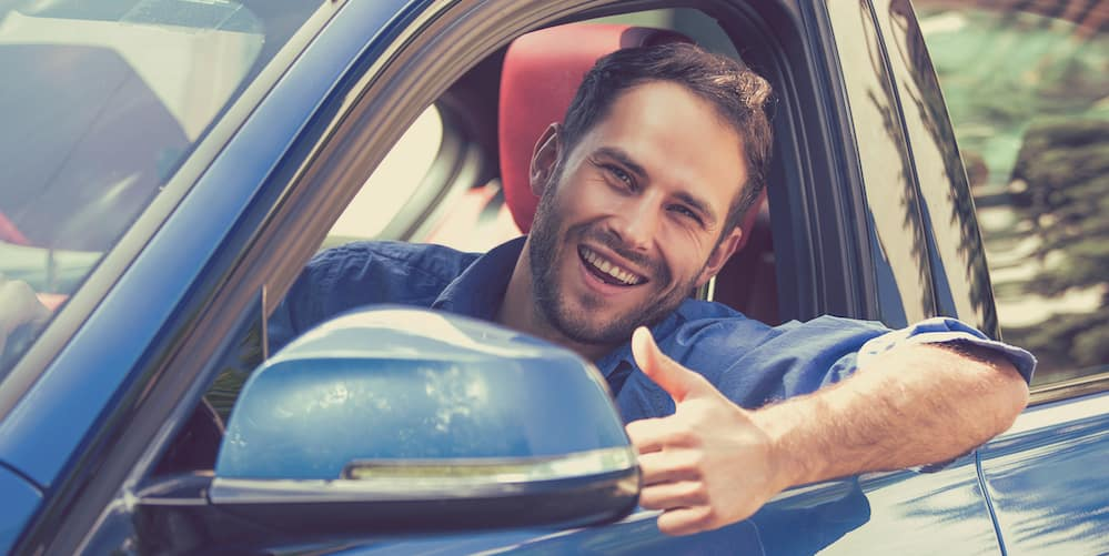 Man Giving a Thumbs Up After Buying a Used Car