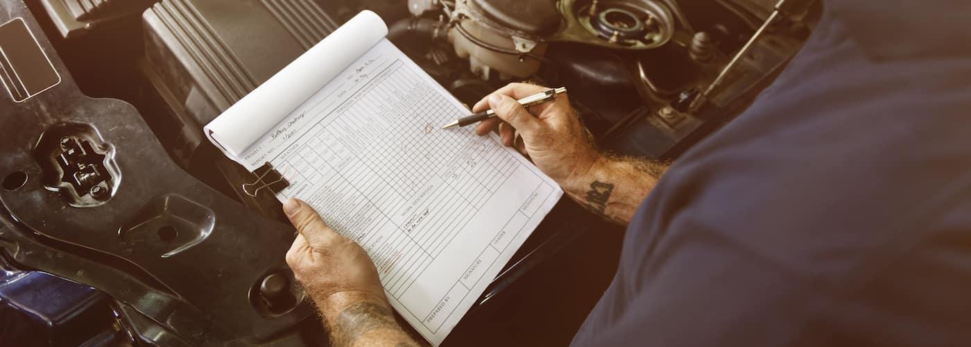 Mechanic Going Over a Checklist