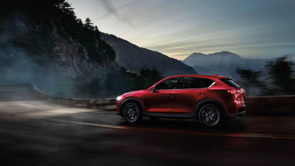 Red Mazda CX-5 driving on a foggy road