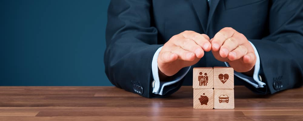 Insurance concept. Businessman with protective gesture and insurance icons on wooden cubes: family and life, health, financial, and car insurance.