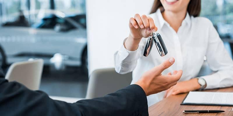 Woman handing man car keys