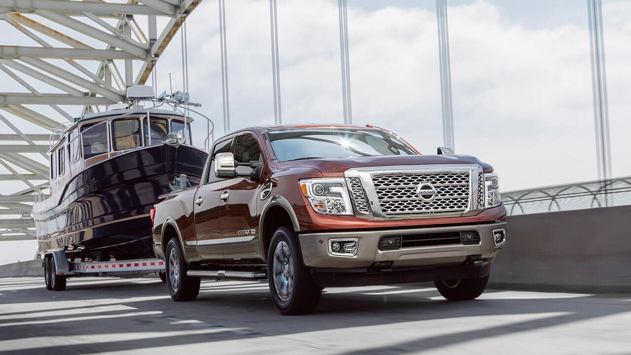 Nissan Titan XD Towing A Boat Across A Bridge