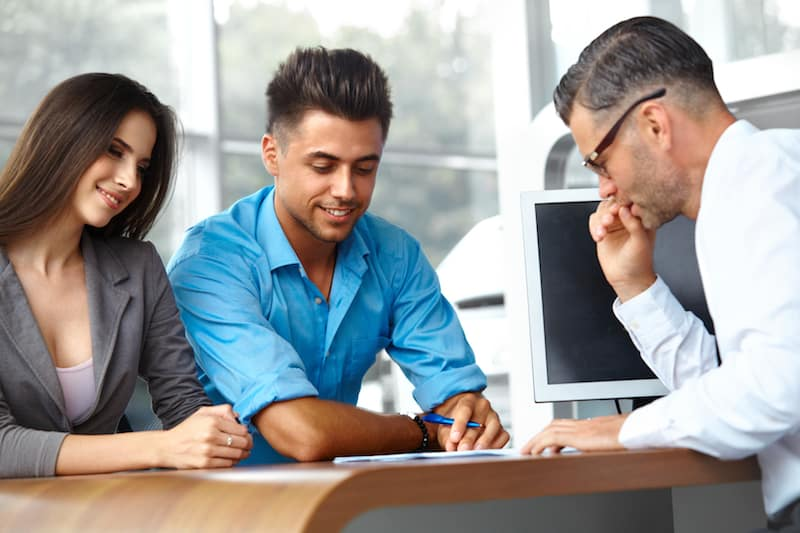 Young couple going over car sales contract with dealer