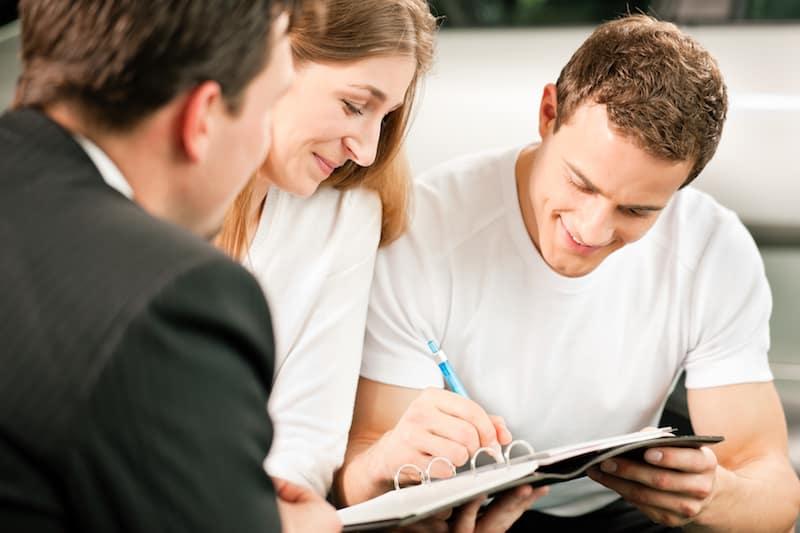 Couple signing paperwork as dealer holds car keys