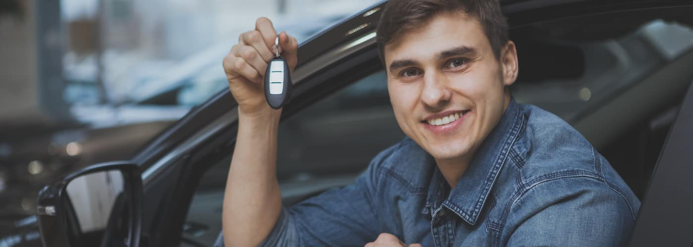Man Holding New Car Key in Car