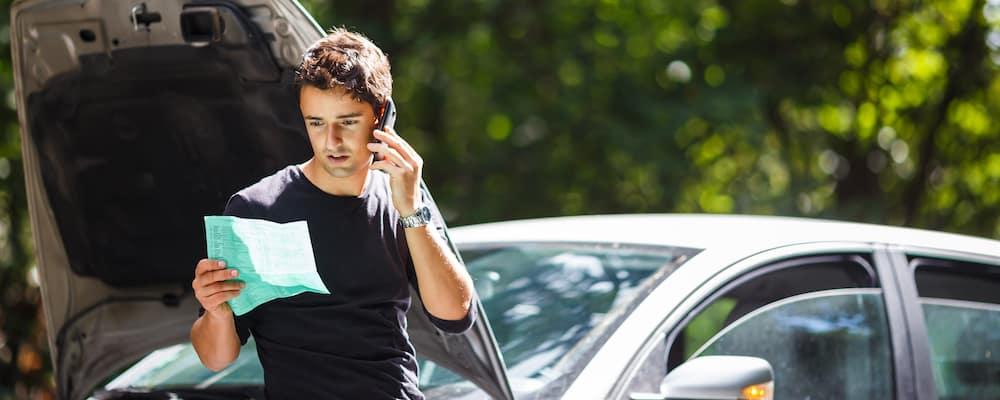 Man Calling Roadside Assistance Next to Broken Down Car