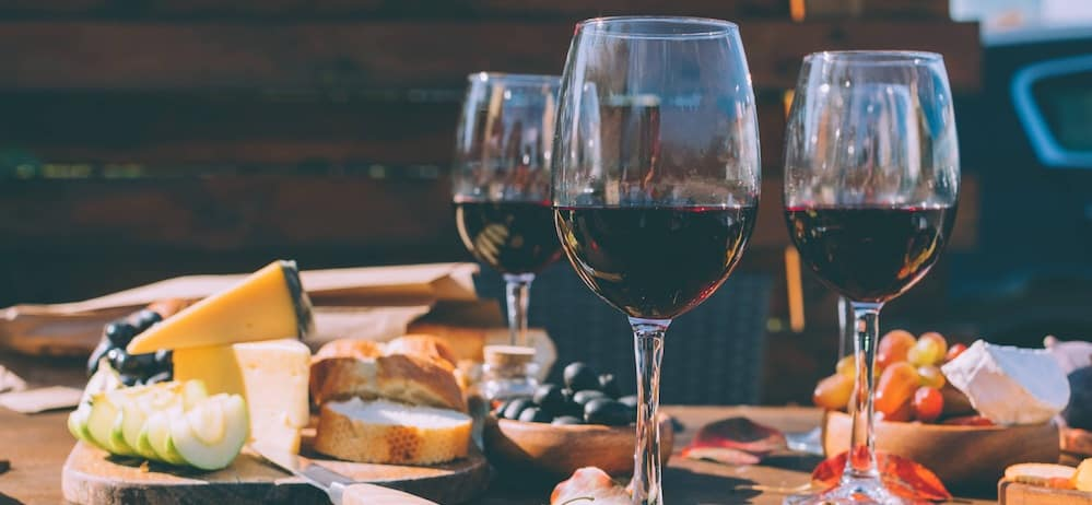 Glasses of red wine on a table next to a meat and cheese plate and other food