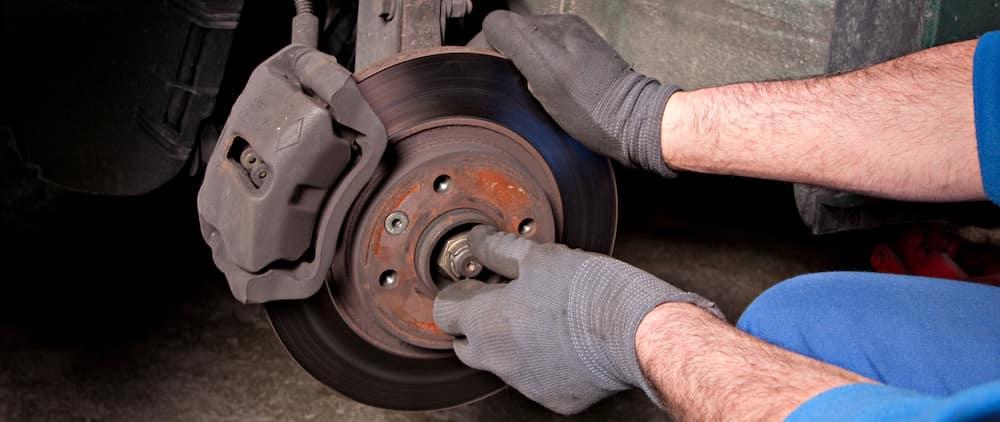 Auto mechanic repairing brakes