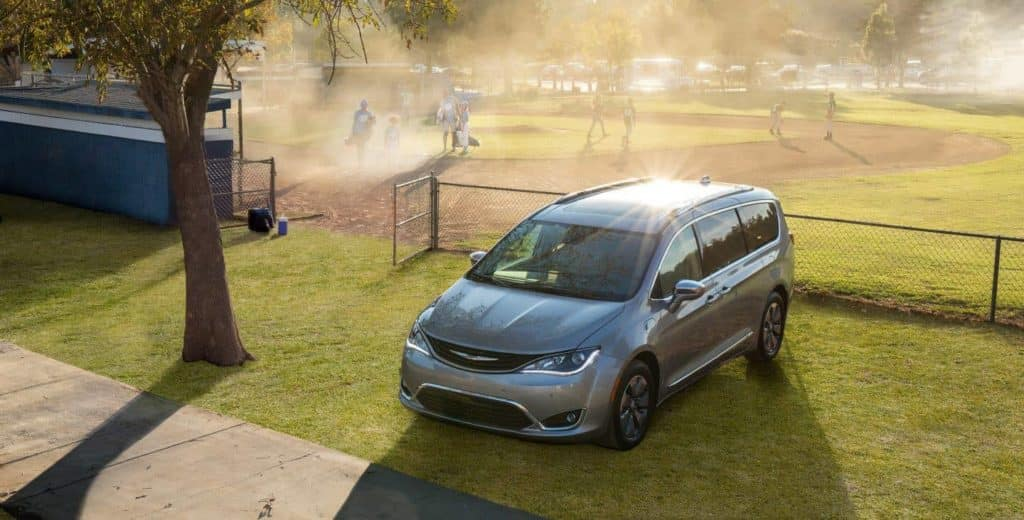 Silver 2018 Chrysler Pacifica parked by a baseball field