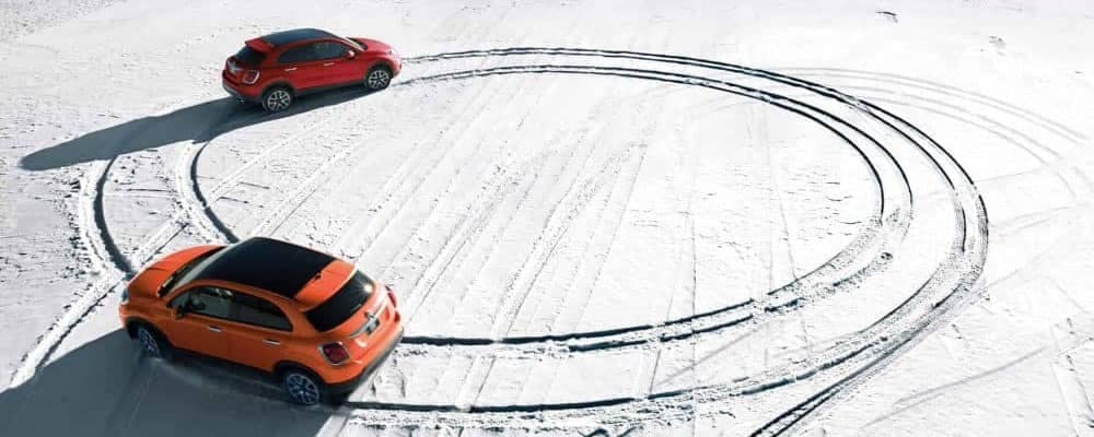 Two fiat models doing donuts in the snow
