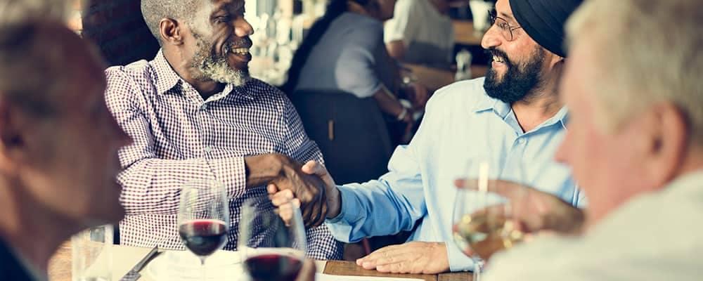 Business associates having dinner and shaking hands