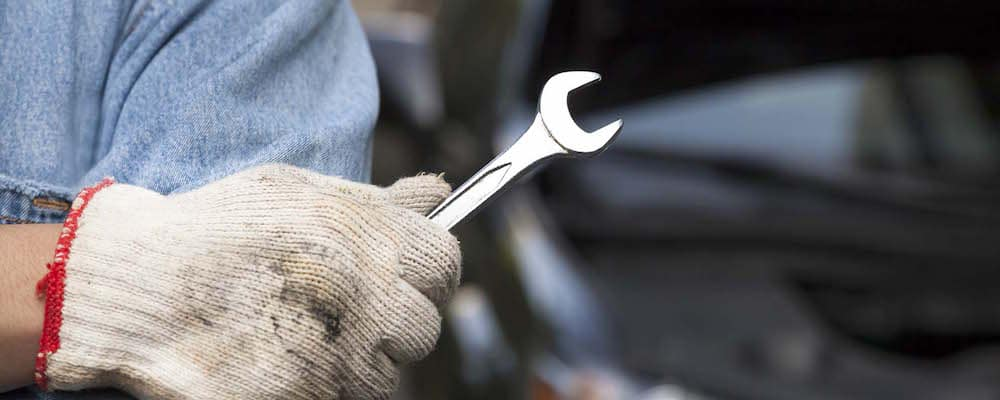 Mechanic with gloved hand holding wrench
