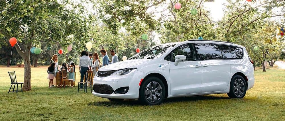 A 2020 Chrysler Pacifica parked on a lawn at a family picnic