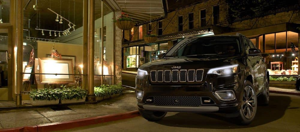 A 2020 Jeep Cherokee driving downtown in a city at night