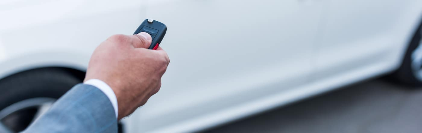 A man using a Dodge key fob to unlock his vehicle.