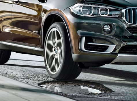 Close up of BMW vehicle in front of pothole
