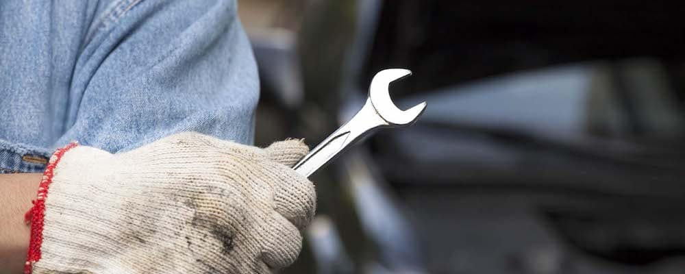 close up of gloved hand holding wrench