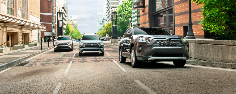 Three 2019 Toyota RAV4 Crossovers in Different Colors Driving in City