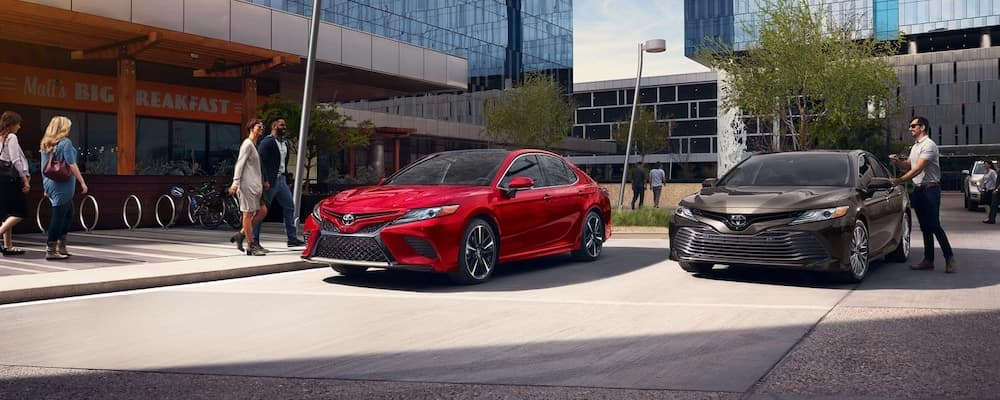 Red 2019 Toyota Camry and brown 2019 Toyota Camry in parking lot