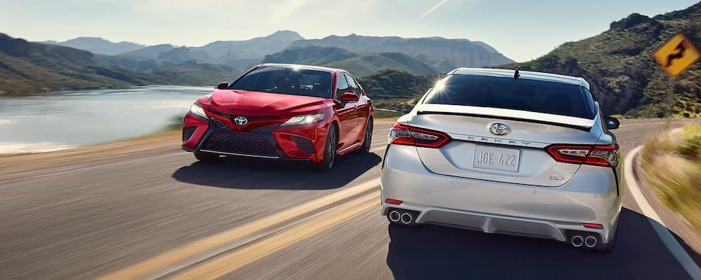 Red 2019 Toyota Camry and white 2019 Toyota Camry passing each other on mountain highway