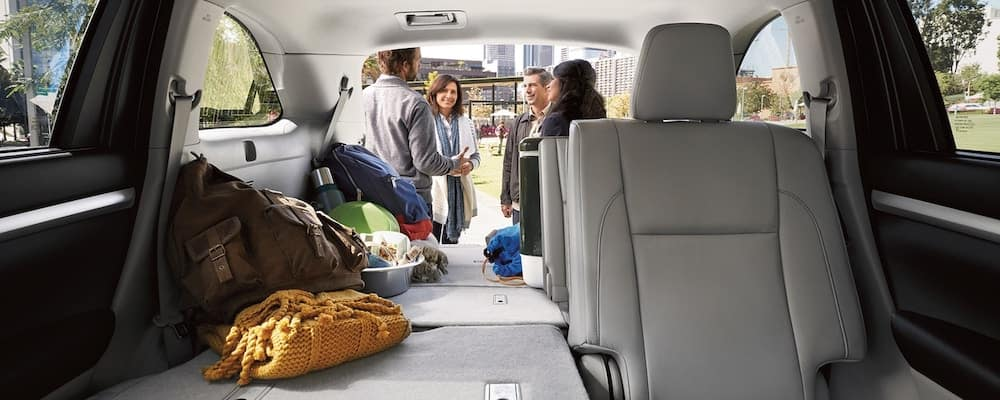 2019 Toyota Highlander cargo space with 60-40 split fold rear seats down and people gathered in background