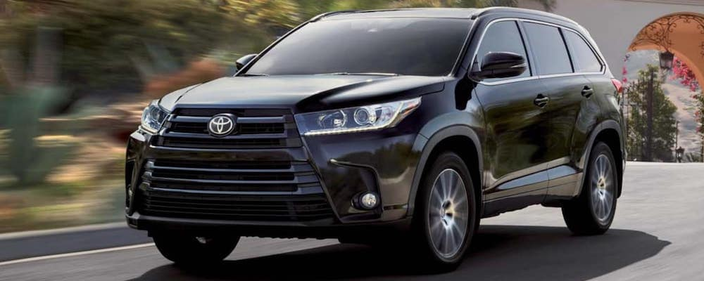 Black Toyota Highlander driving in sunny area from front