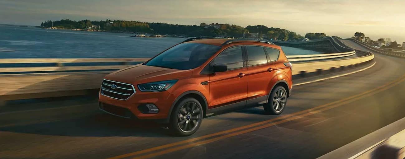An orange 2019 Ford Escape driving over a bridge at sunset