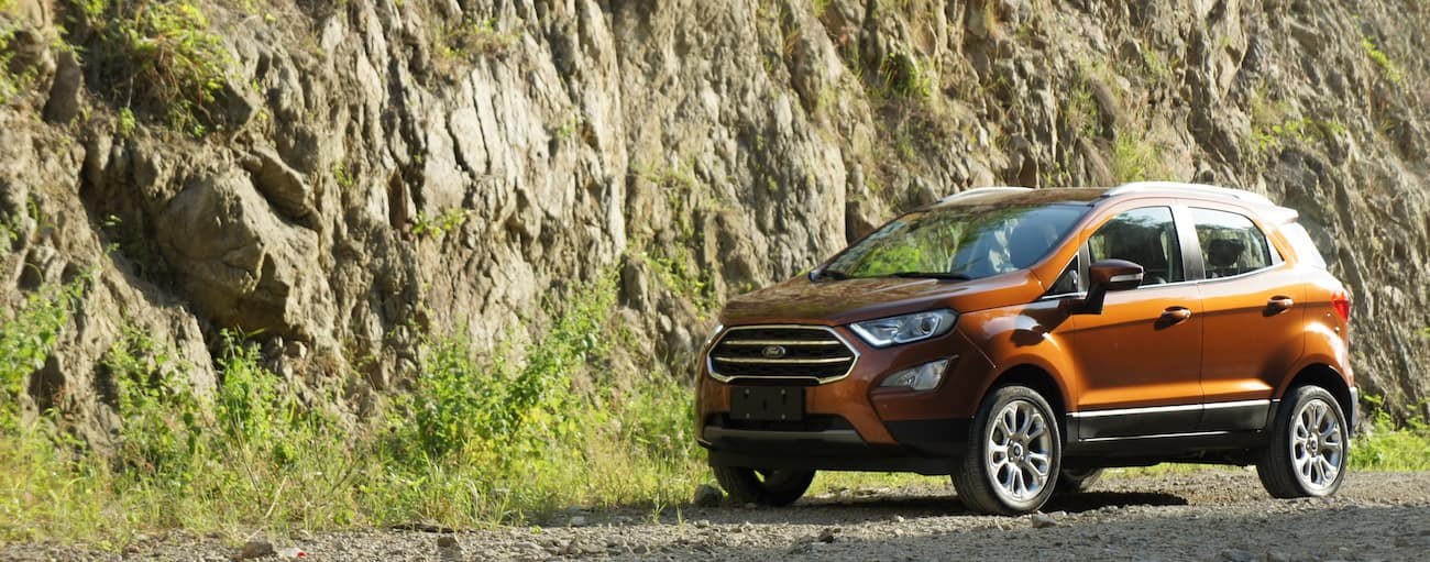 A bright orange 2019 Ford EcoSport parked next to a rock ledge