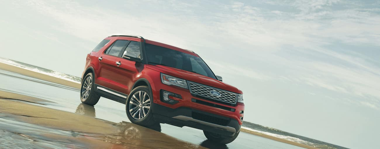 A red 2019 Ford Explorer parked on a sandy beach