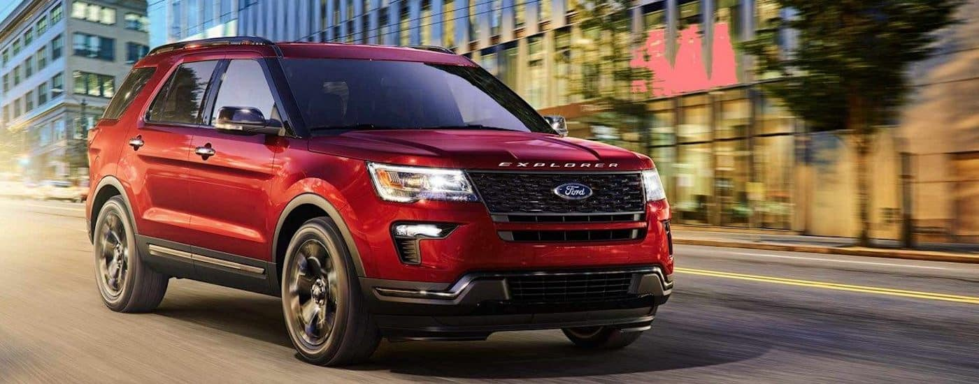 A dark red 2019 Ford Explorer cruises a city street at dusk