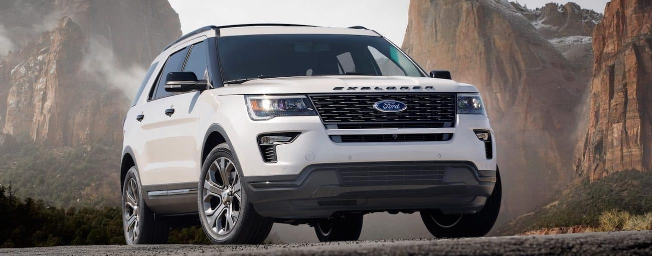 The 2019 Ford Explorer in white with rugged mountains in the background