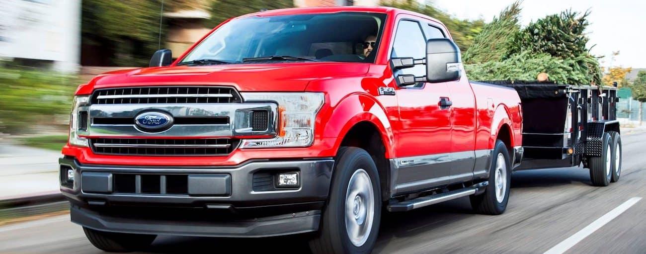 A red 2019 Ford F-150 tows a black metal trailer down a suburban street