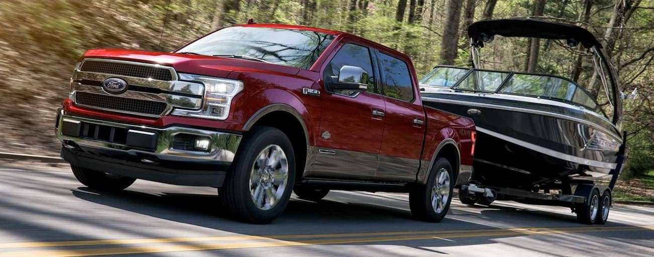 Dark red 2019 Ford F150 towing boat on wooded road