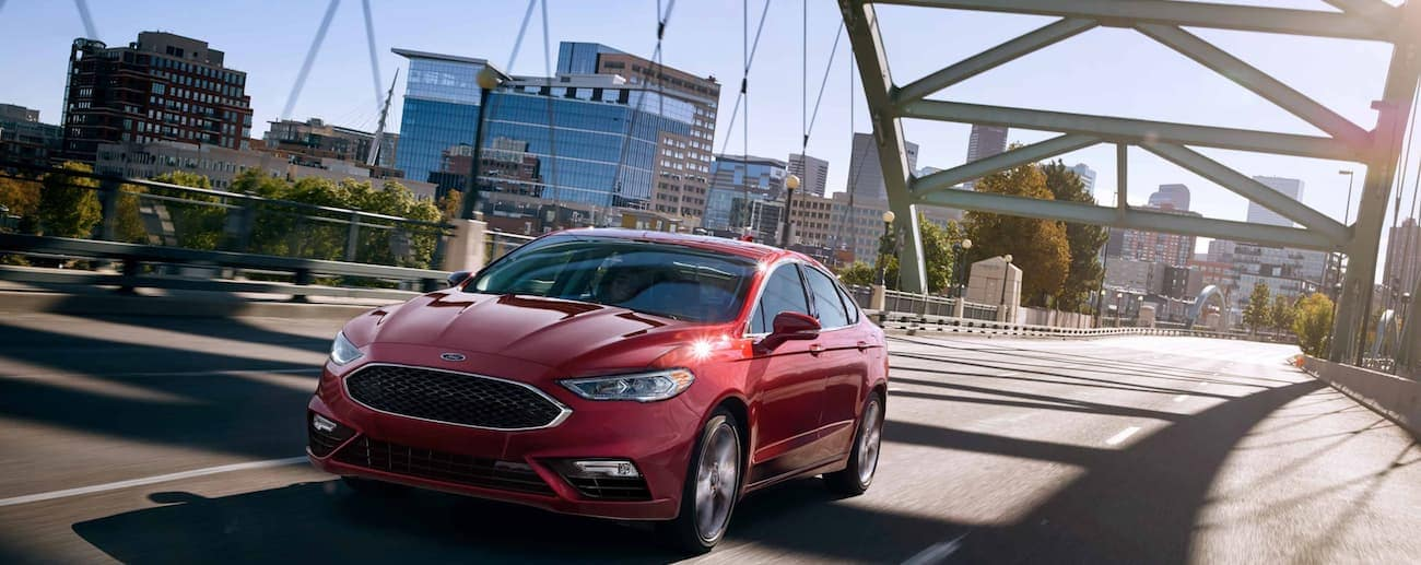 A deep red 2019 Ford Fusion speeds over a Ohio bridge